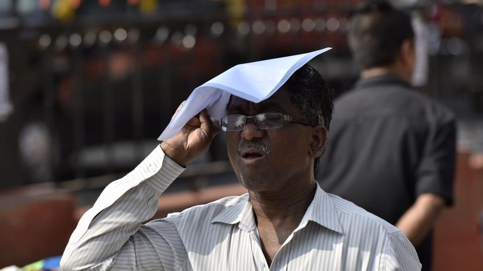 A man struggles in the scorching heat, hides his face with a plastic file in Mumbai on Wednesday.