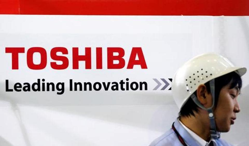 An employee stands next to a logo of Toshiba Corp in Yokohama, south of Tokyo.