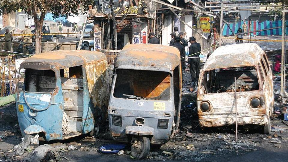 Charred vehicles at the site of a blast in Delhi's Sarojini Nagar in 2005.