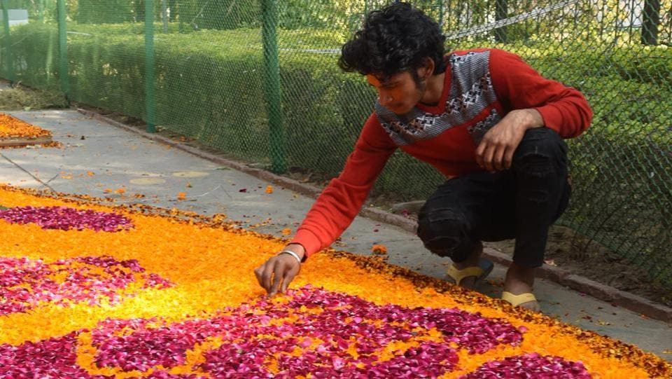 A man preparing a rangoli with flowers at Rose Garden in Chandigarh on Friday. (Sanjeev Sharma/HT Photo)