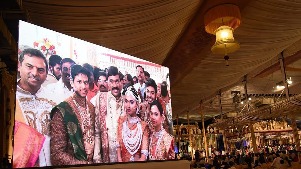 Controversial mining tycoon, Gali Janardhan Reddy, (C) is seen on a big screen as he poses with his daughter Bramhani (2R) and son-in-law, Rajeev Reddy (2L) during their wedding at the Bangalore Palace Grounds in Bangalore.  Reddy took over a royal palace and flown in Brazilian dancers at a reported cost of 75 million dollars to celebrate his daughter's wedding.