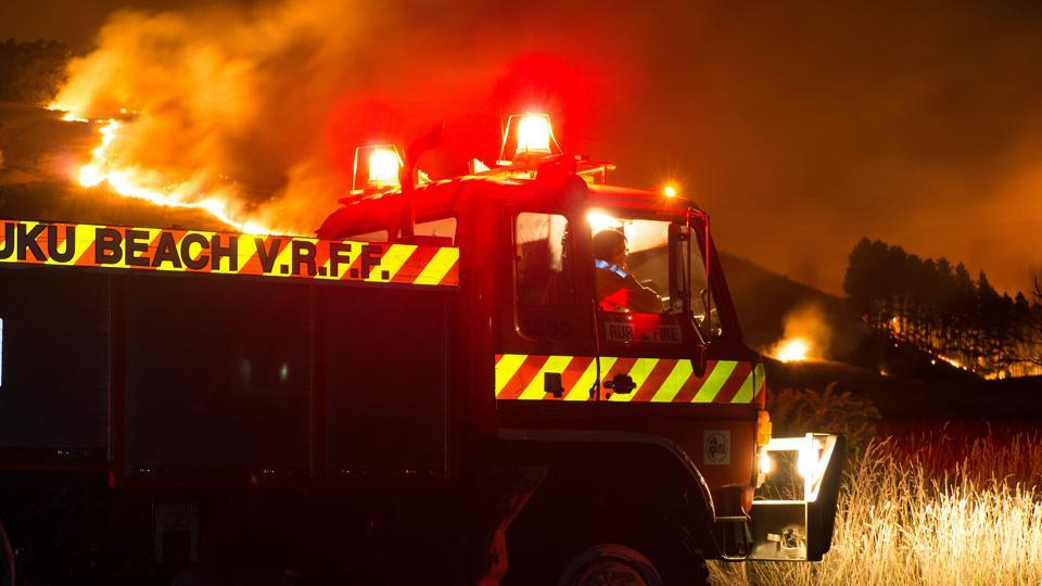 Firefighters combat the wildfires along Worsleys Road in Christchurch before sunrise on February 16, 2017. 200 firefighters were operating about 45 pumps and tankers on the ground, with police and the military also providing additional personnel for the emergency response. (Oliver WATSON / AFP)