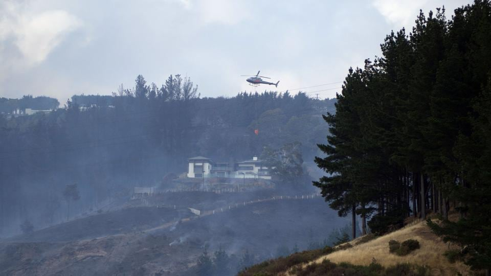 A helicopter dousing the fire in Christchurch early on February 16, 2017.  (Oliver WATSON / AFP)