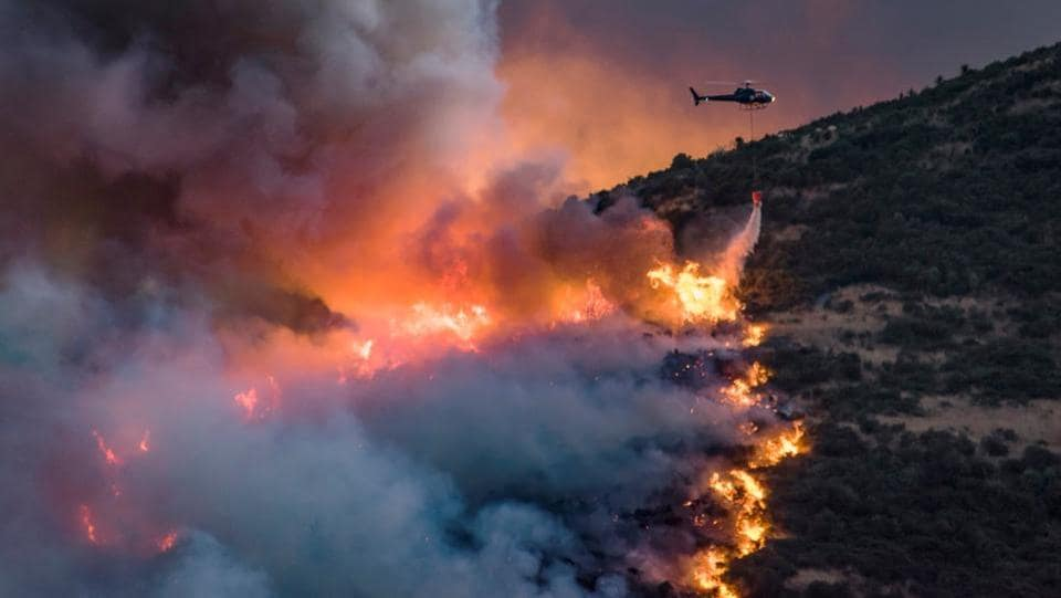 A helicopter dumps fire retardant on wildfires near Christchurch in New Zealand.  Fourteen helicopters and three planes were helping battle the blaze, the maximum number of aircraft that could safely operate around the fire-front at one time.  (Mark Hannah  / REUTERS)