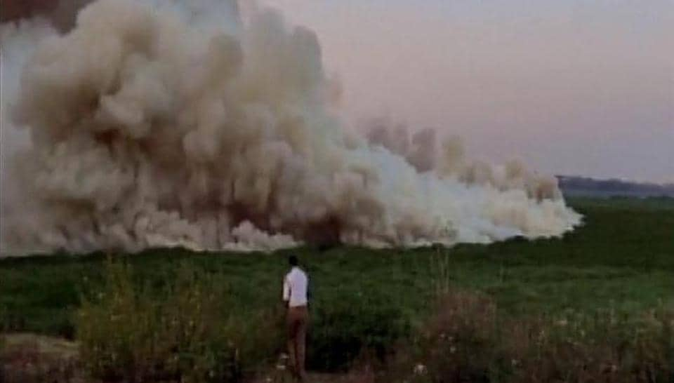 An official stands by as smoke billows from Bellandur lake in the IT belt of the Bengaluru.