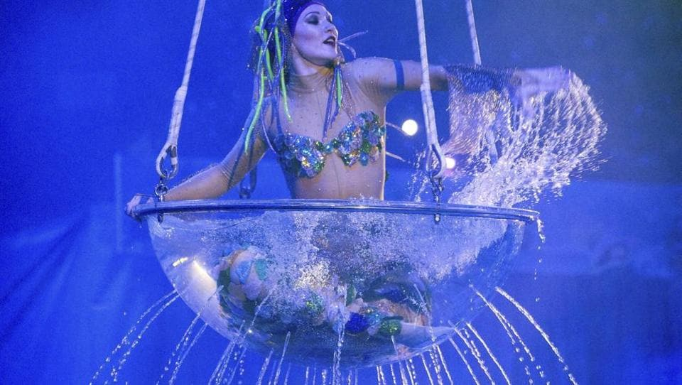 An artist performs sitting inside a transparent bowl full of water at a new circus show called
