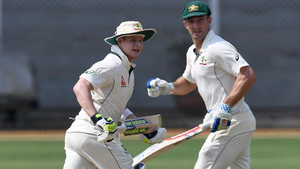 Australia's captain Steve Smith (L) and Shaun Marsh run between the wickets during the first day of three-day practice cricket match between India 'A' and Australia at The Brabourne Cricket Stadium.