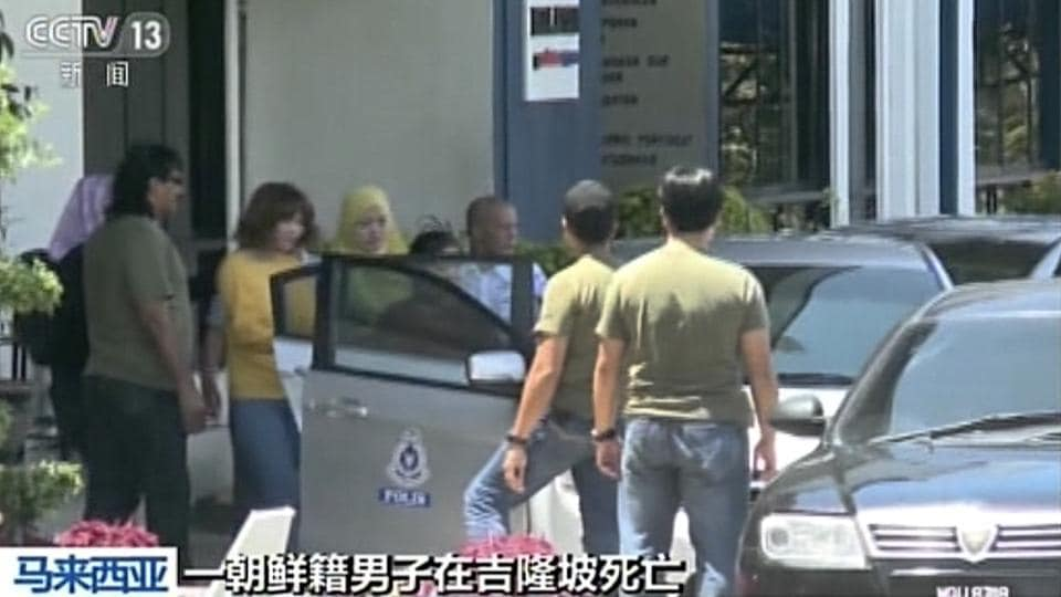 A woman wearing a yellow top, fourth from left, suspected of involvement in the apparent assassination of Kim Jong Nam, the half brother of North Korean leader Kim Jong Un, is escorted by Malaysian officials to a vehicle in Kuala Lumpur.