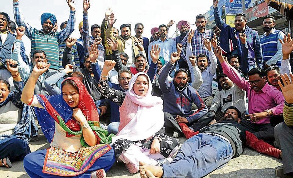 Members of the Punjabi University Employees Union blocking the national highway in front of the university in Patiala on Friday.