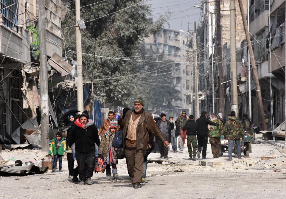 Syrian residents flee violence in Aleppo's eastern al-Salihin neighbourhood on December 12, 2016 after regime troops retook the area from rebel fighters.