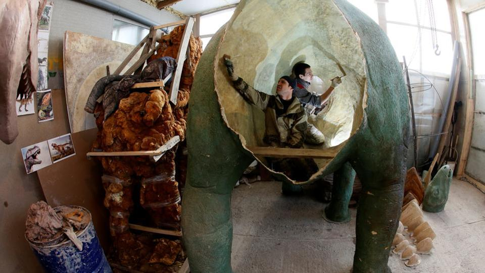Assistants of businessman Vitaly Yan-Vin-Tin (not pictured) working on a polyurethane and fibreglass sculpture of a dinosaur in the Siberian village of Beryozovka outside Krasnoyarsk, Russia on February 17, 2017.  (Ilya Naymushin / REUTERS)