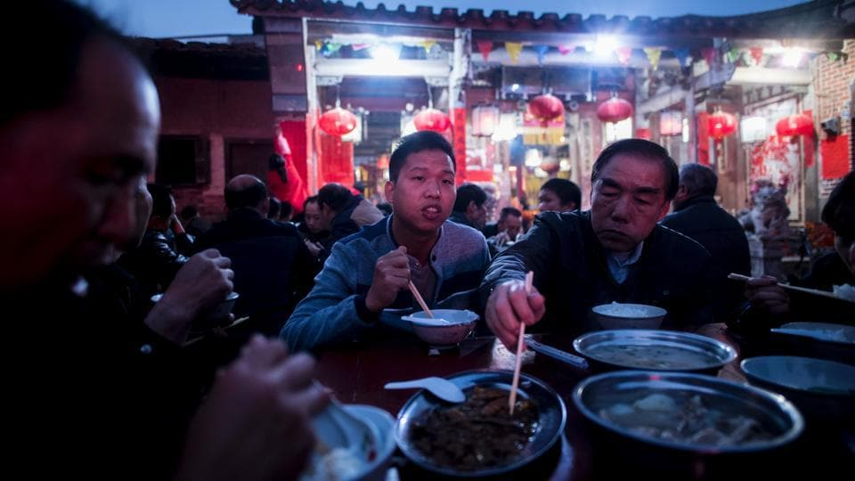 Zheng Yinquan (C) having dinner in front of the temple before performing the 'eating flowers' ritual. (Johannes EISELE / AFP)