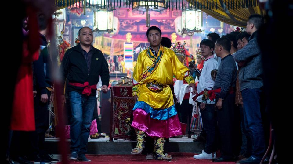 Villager getting ready to perform the 'eating flowers' ritual. The ceremony in the village of Fangshan begins when eight local men selected by village elders don ancient-style Chinese dress to pray in a temple for protection from the Buddha. (Johannes EISELE / AFP)