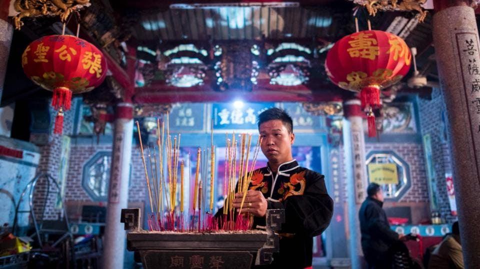 Zheng Yinquan burning incense before performing the 'eating flowers' ritual.  (Johannes EISELE / AFP)