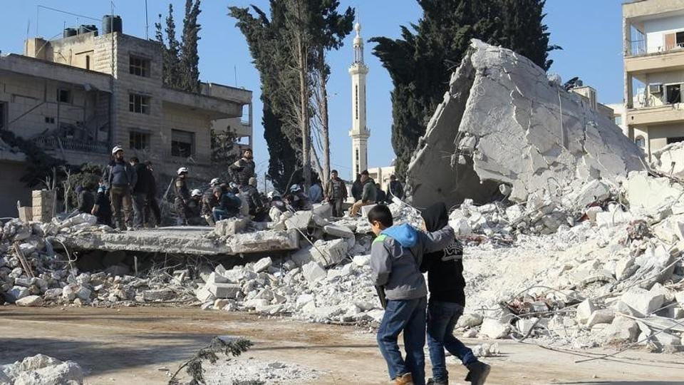 Children walk at the site hit by airstrikes in the rebel-held city of Idlib, Syria.