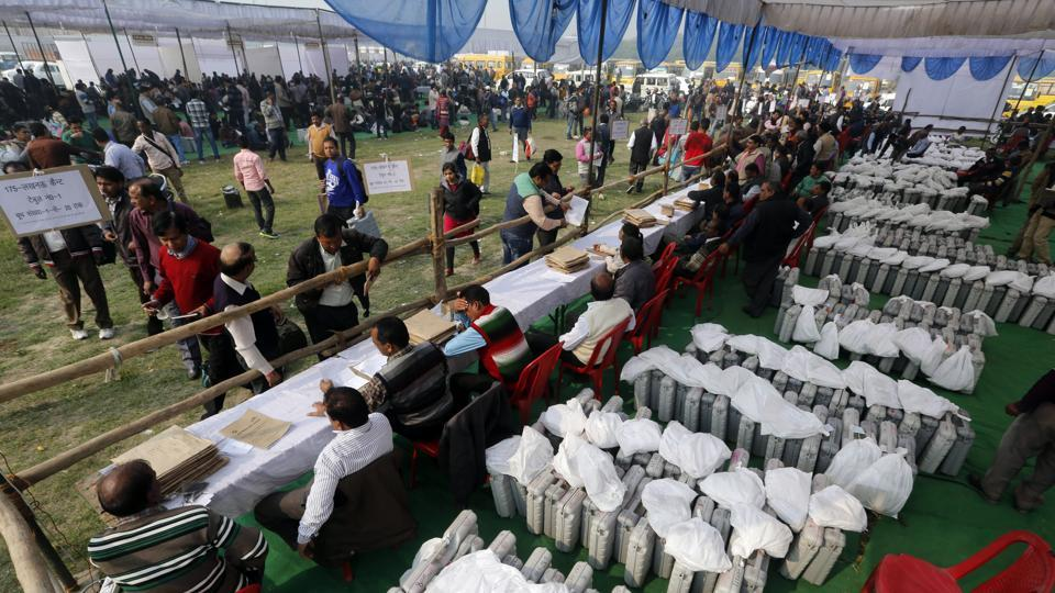 Election officers gather at a distribution center to receive electronic voting machines for their respective polling stations on the eve of polling in Lucknow, India, Saturday, February 18, 2017.