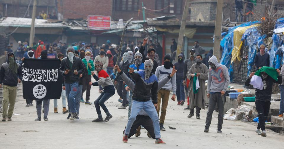 Protesters wave an ISIS flag and throw stones at security forces during clashes in Srinagar on Friday.