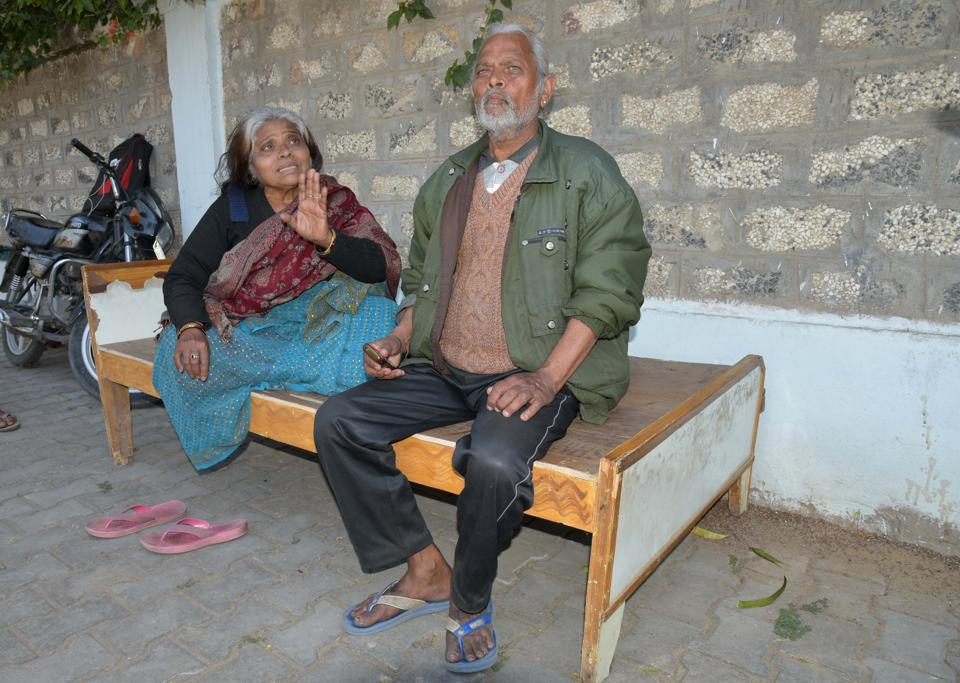 Shammirani Bhargav (left) and her husband Narayan Das Bhargav sit on a cot on a pavement opposite the house from which they were evicted on February 11.
