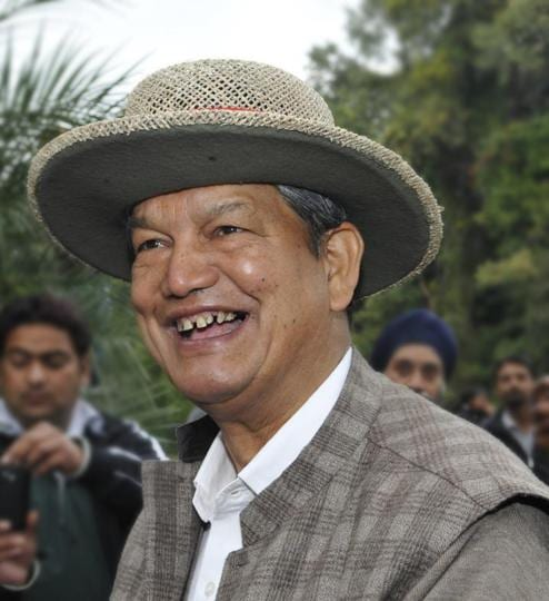 Chief minister Harish Rawat pose for camerapersons in Dehradun.