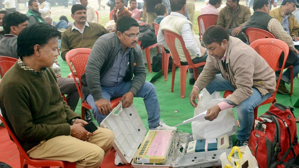 Election officials check EVMs on the eve of the third phase of the UP assembly polls in Lucknow on Saturday.