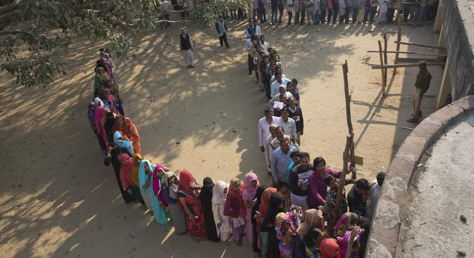 People stand in a queue to cast their votes at a village near Amroha in Uttar Pradesh on Feb 15.