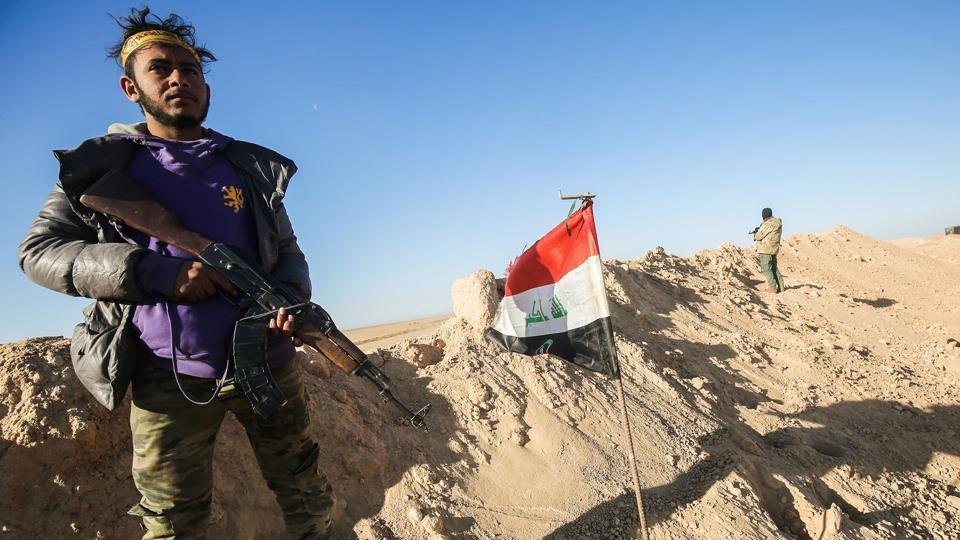 A fighter of the Hashed al-Shaabi (Popular Mobilisation) paramilitaries poses for a picture carrying a Kalashnikov assault rifle next to an Iraqi flag at a defensive position near the frontline village of Ayn al-Hisan, on the outskirts of Tal Afar west of Mosul.