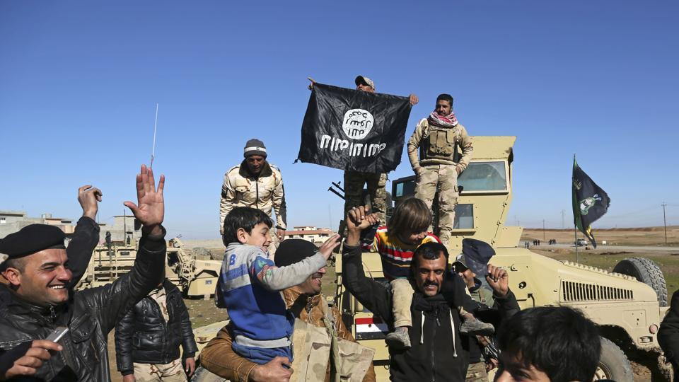 Iraqi army soldiers celebrate with residents of liberated neighbourhoods as they hold upside down a flag of the Islamic State group, in the eastern side of Mosul, Iraq.
