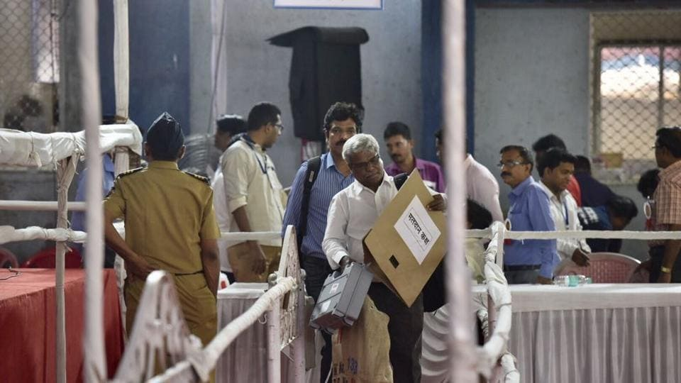 CAN'T TAKE EYES OFF: Polling officials get EVMs at Ghatkopar on Monday. (ARIJIT SEN/HT)