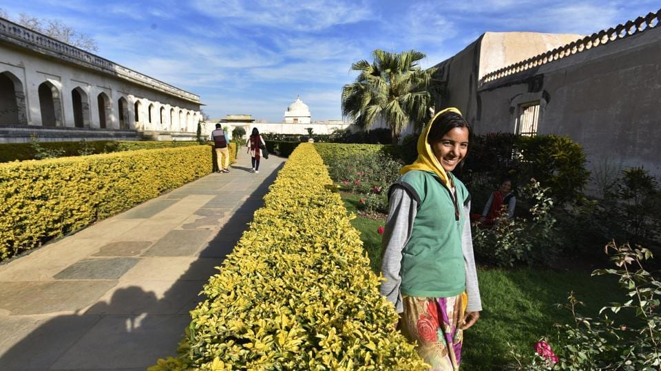 A tourist smiles for the camera at the rose garden inside Padmavati's mahal.  (Raj K Raj/HT PHOTO)