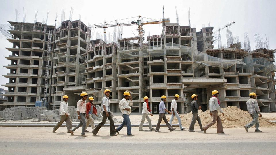 Workers walk in front of the construction site of a commercial complex outside Ahmedabad