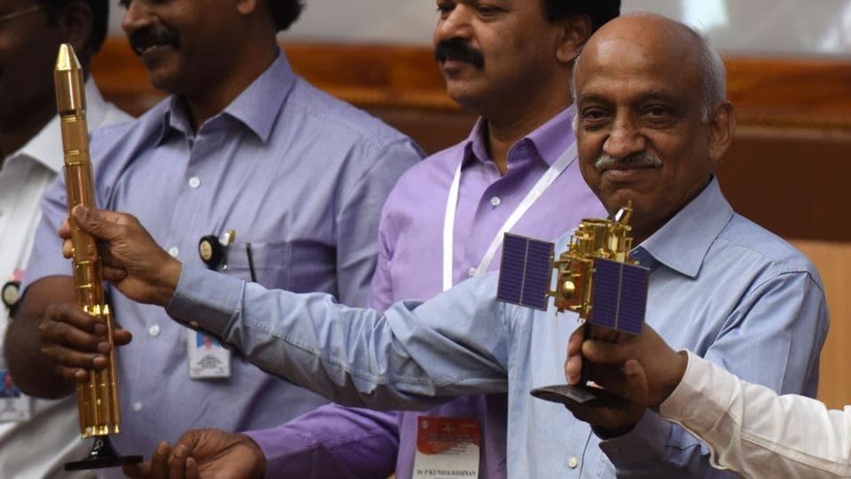 ISRO chairman Kiran Kumar Rao (R) displays models of the CARTOSAT-2 and Polar Satellite Launch Vehicle (PSLV-C37) as he speaks to media after the launch of the Polar Satellite Launch Vehicle (PSLV-C37) at Sriharikota on Febuary 15.