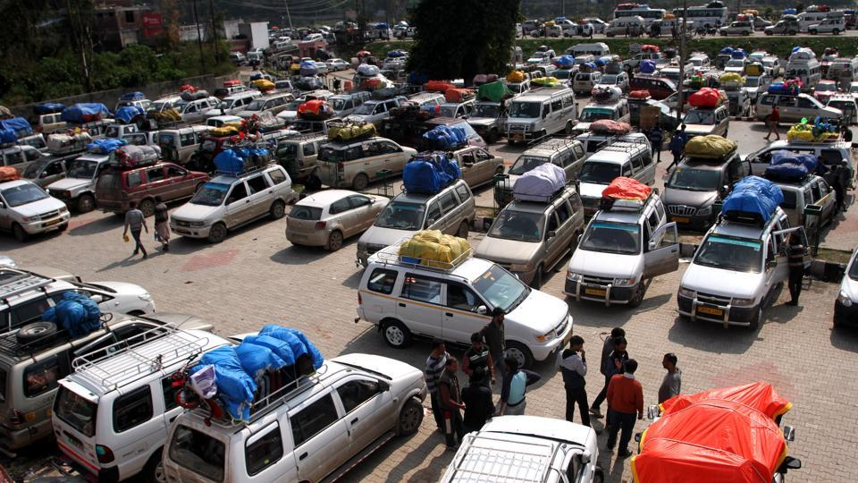 Passengers sit outside stranded vehiclesin Jammu as they wait for the opening of the Jammu-Srinagar national highway.
