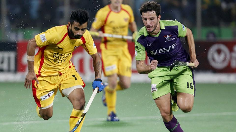 A Ranchi Rays player (in yellow) vies for the ball with a Delhi Waveriders (green) player in Tuesday' Hockey India League match. Ranchi won but were still eliminated while Delhi have qualified for the semis.