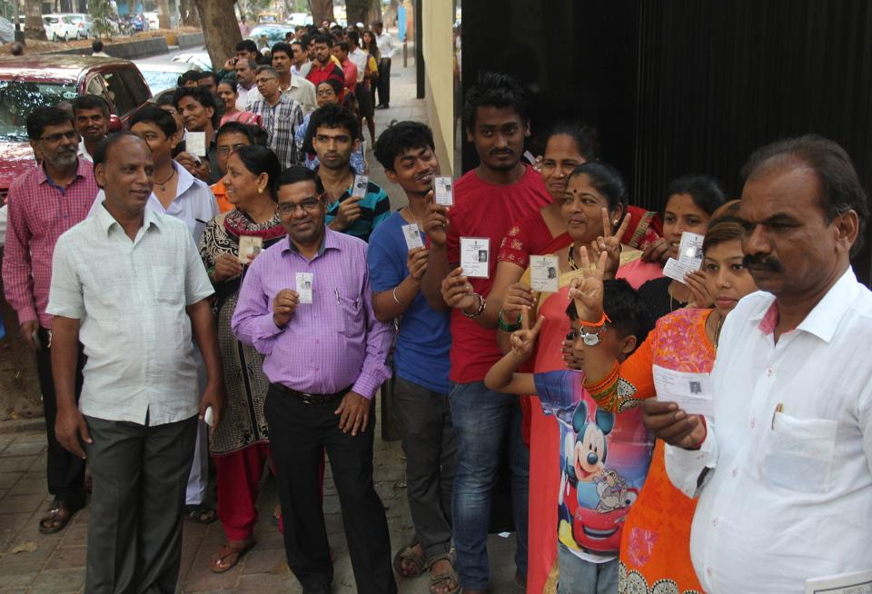 People stand in a queue to cast their vote outside a polling both at Cuffe Parade.