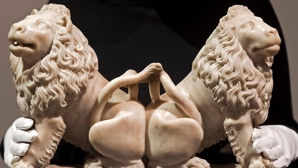 An employee poses for a photograph with a re-discovered sculpture of two carved marble lions, by French artist Andre Beauneveu, commissioned by French King Charles V, at Christie's auction house in London on February 20.