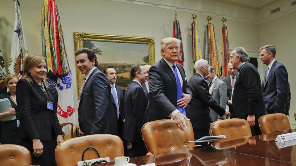 President Donald Trump tosses his folder on the table before the start of a meeting with automobile leaders in the Roosevelt Room of the White House in Washington on January 24, 2017. From left are, GM CEO Mary Barra, Ford Motors CEO Mark Fields, Fiat Chrysler Automobiles president and CEO Sergio Marchionne.