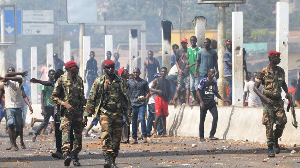 Soldiers walk in a street during a protest of teachers asking for wage increase and more hiring on February 20, 2017 in Conakry.