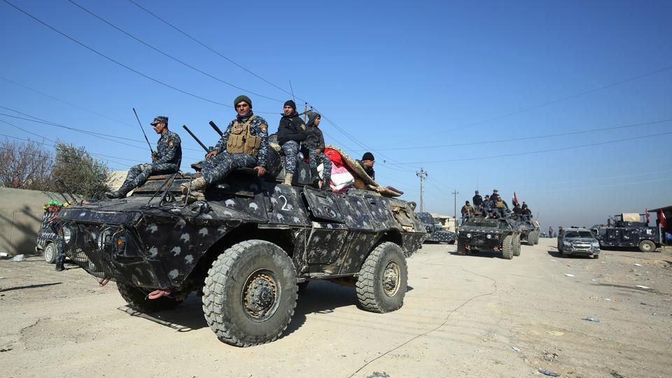 Iraqi security forces advance in the village of al-Buseif, south of Mosul, during an offensive to retake the western side of the city from Islamic State (IS) group fighters on February 21, 2017.