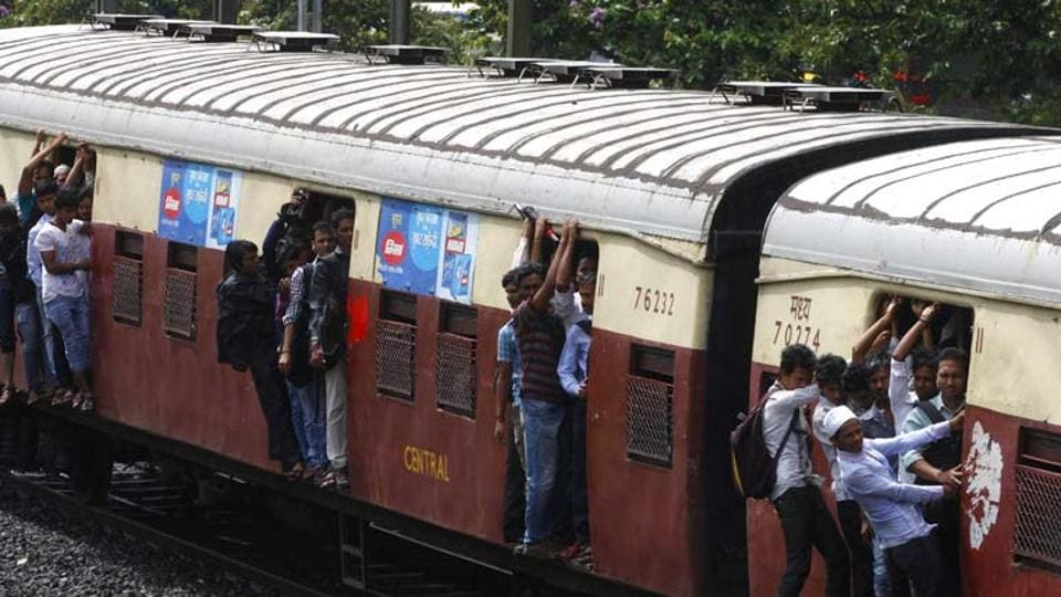 Passengers travel on the footboards of a suburban local train in Mumbai.