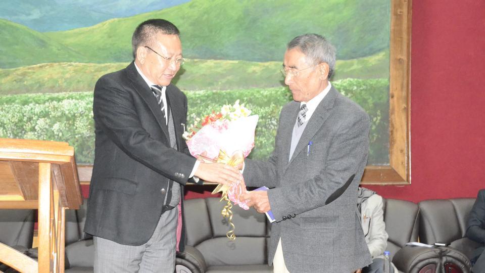 Former Nagaland chief minister TRZeliang (left) presents a bouquet to Shurhozelie Liezietsu (right).