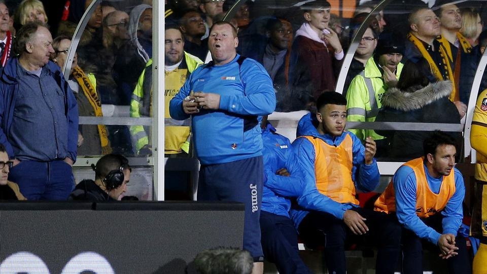 Sutton United's substitute Wayne Shaw eats a pie during a FA Cup match against Arsenal.