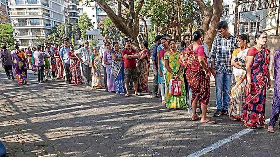 People wait outside a polling booth at juhu on Tuesday.