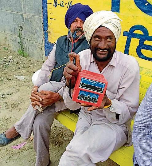 A farmer holding an auto-start switch used for tubewells
