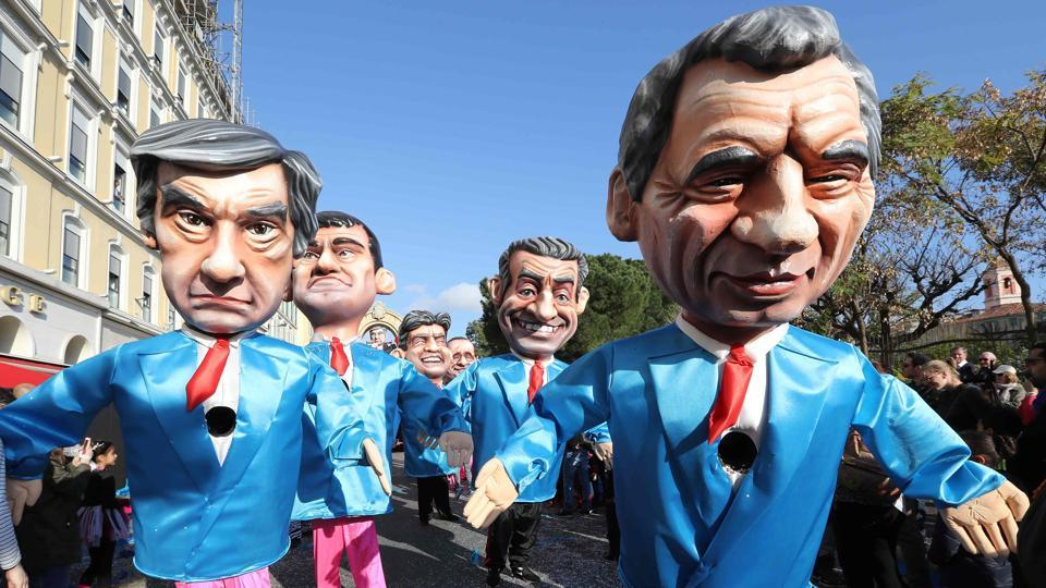 Artists dressed up with costumes depicting French presidential election candidate for the right-wing Les Republicains (LR) party Francois Fillon (L) and president of the center right party Modem Francois Bayrou (R) followed by former Prime Minister Manuel Valls (back,L) and former French president Nicolas Sarkozy in the streets of Nice . (VALERY HACHE / AFP)