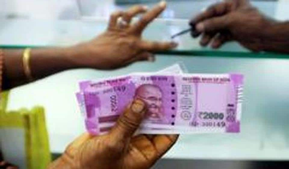 An Indian woman holds Rs 2000 notes as she has her finger marked with indelible ink at a bank in Chennai. The tax department has been closely monitoring bank deposits since the demonetisation of Rs 500 and Rs 1000 notes on November 8.