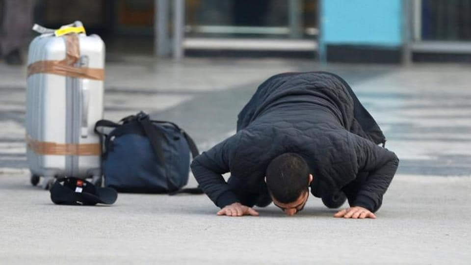 An Afghan, whose asylum application has been rejected, kisses the ground after he arrived from Germany in Kabul airport.
