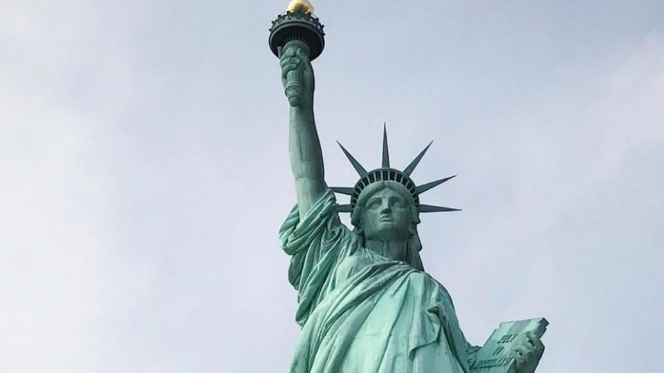 A giant banner saying 'Refugees Welcome' hangs on the pedestal of the Statue of Liberty on Tuesday.