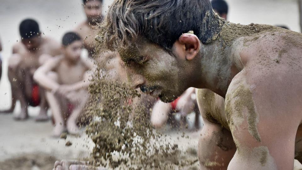 Wrestler smearing mud over himself before 'Kushti' (wrestling) at Krishan Pehalwan Akhaara (P and T) facility in Amritsar on Wednesday. (Gurpreet Singh/HT Photo)