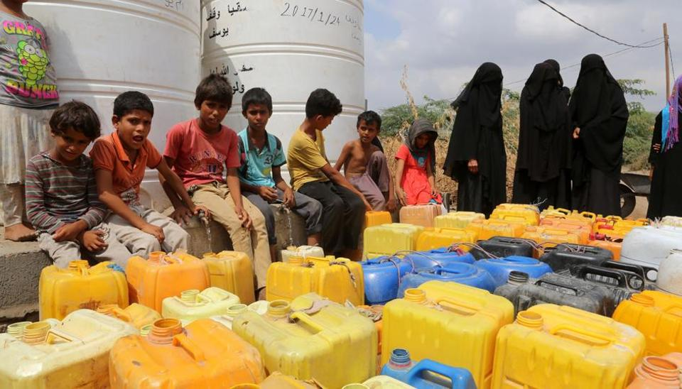 Yemenis collect water from a donated source amid continuing wide spread disruption of water supply in the impoverished coastal village on the outskirts of the Yemeni port city of Hodeidah, on February 20, 2017.