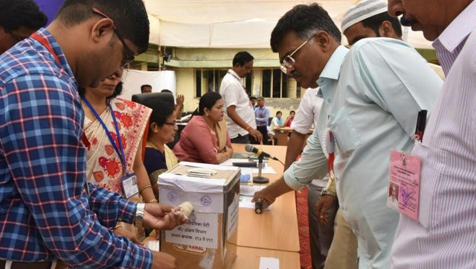 Polling officers open postal ballot boxes as the counting for BMC elections begin, at Global Mill compound in central Mumbai on Thursday.